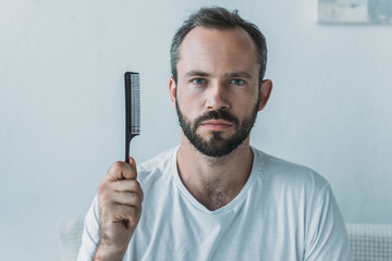 bearded mid adult man holding comb and looking at camera, hair loss concept