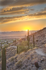 A hiking trail on the side of a mountain heading into an Arizona sunset.