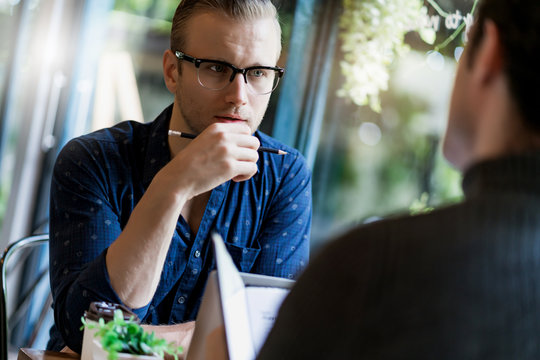 two smart caucasian man meeting and consult with serious and focusing conversation near window cafe background