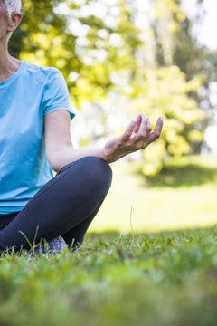Senior woman in yoga lotus pose in park