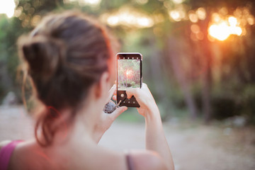 Girl making a photo at sunset in the woods
