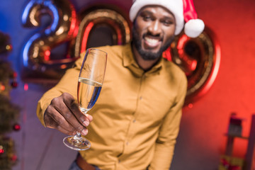 happy african american businessman in santa hat showing glass of champagne at new year corporate party