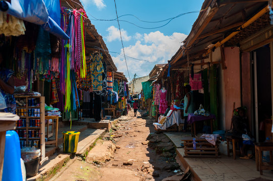 view of colorful open air street market in doula cameroun during sunny day with traditional clothes