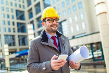 Architect in protective helmet using phone in front of office building