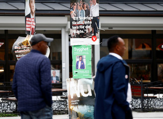 People walk past election campaign posters in the Rinkeby neighbourhood in Stockholm