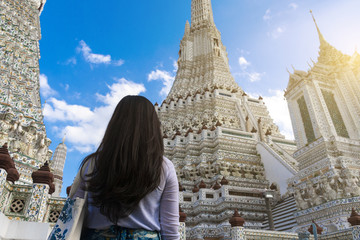 Wall Mural - Woman tourist is looking at the Pagoda inside Wat Arun temple in Bangkok, Thailand during holiday vacation time.