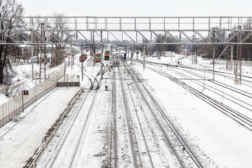 Railway station in winter, in the background people clean snow