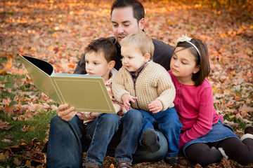 Father Reading to His Children in Autumn Park