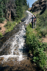 Father and son next to the waterfall. Rex Falls. Rio Grande National Forest,  Colorado, US