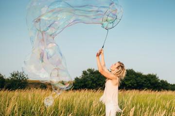 Girl doing soap show at sunset. Original genre. Large soap bubbles