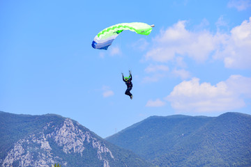 parachutist descends against a blue sky, in the background the mountains