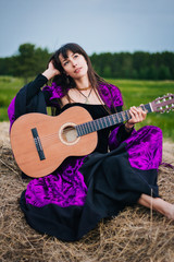 A beautiful girl musician with long black hair sits on a haystack in a medieval dress. In a purple suit plays a song on a guitar in the background of the forest. Gipsy with a guitar