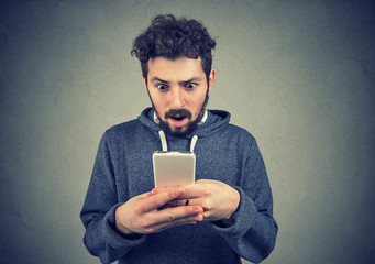 anxious young man looking at mobile phone seeing bad news