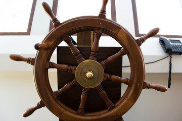 Front view of wooden rudder on a sailing ship inside the capitan's cabin