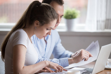 Serious millennial couple read documents managing house utility bills, man and woman analyze bank notice or insurance considering terms, husband and wife hold papers calculating finances or budget