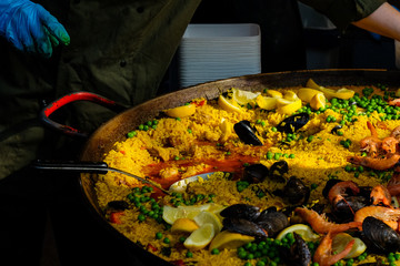 A fresh large pan of paella is ready to eat.