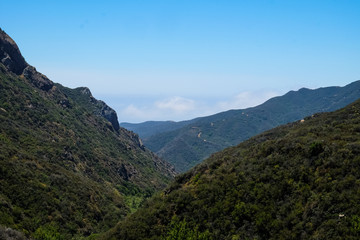 Mountains in Malibu, California with a blue sky as fog rolls in on a bright sunny day.