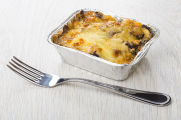 Baked chicken meat with mushroom, mayonnaise in aluminium box, fork