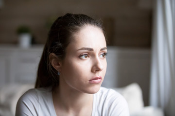 Sad young woman looking in distance thinking about relationships problems, upset hurt girl view from window sorrow about breakup with boyfriend, disappointed female feeling blue having troubles Wall mural
