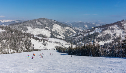 Skiers on the mountain slope on a background of mountains
