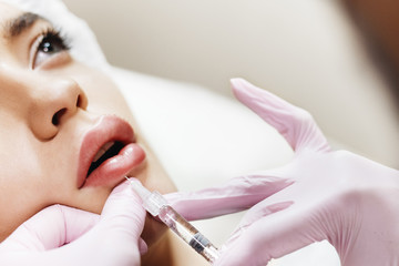 The process of lips enhancement. Cosmetician makes an injection of hyaluronic acid in a beautiful lips. The young girl with a beautiful face in the special hat and hands of the doctor in the pink glov