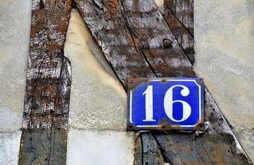 house number 16 on antique rustic wall, old, rusty enamel sign