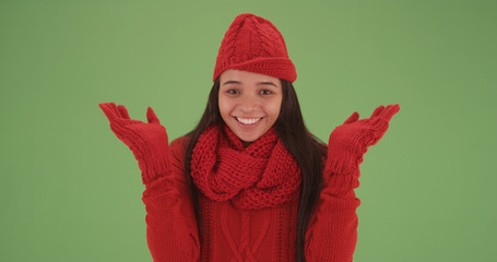 Laughing latina girl in red winter clothes looking happy on green screen