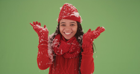 Cheerful latina girl in a red sweater covered in snow on green screen