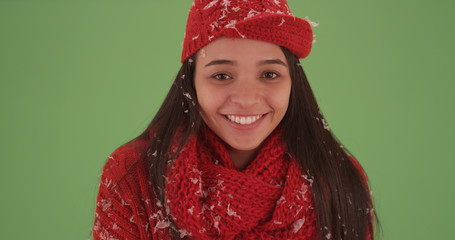 Close-up of millennial latina in red winter clothing on green screen