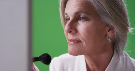Lovely mature caucasian woman applying makeup on greenscreen