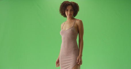 Portrait of pretty black millennial girl looking at the camera on green screen