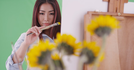 Millennial asian woman artist painting sunflowers on green screen