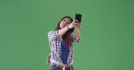 Asian woman taking selfies on her hike on green screen