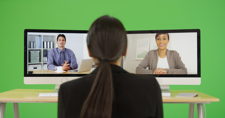 A young businesswoman video chats with her co-workers on green screen