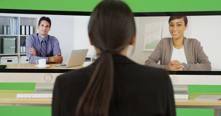 A young businesswoman chats with her office peers on green screen