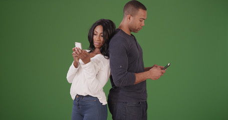 Couple standing back to back texting on cell phones on green screen