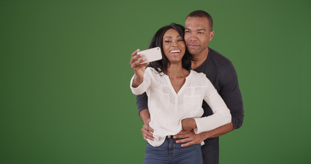 Happy black couple posing for selfies on green screen