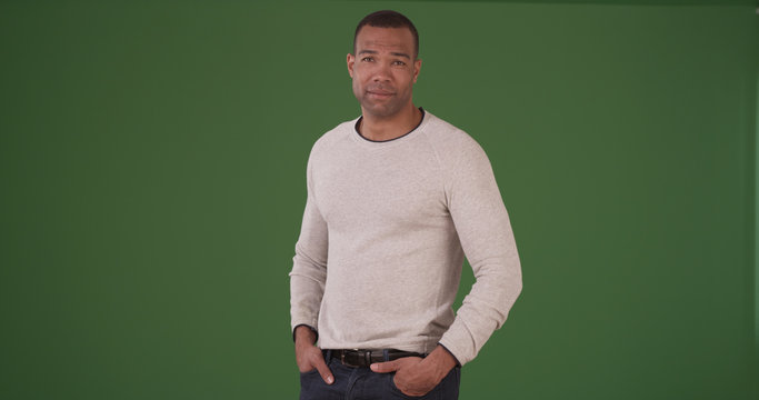 Handsome black man smiling in a trendy white sweater on green screen