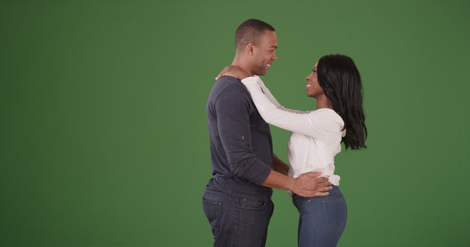 Young black couple sharing intimate moment on green screen