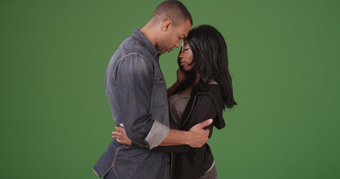 Young black couple sharing tender moment on green screen