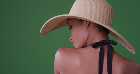 Woman wearing big sunhat with back to camera on green screen