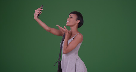 Woman blowing kiss and taking a selfie picture with smartphone on green screen