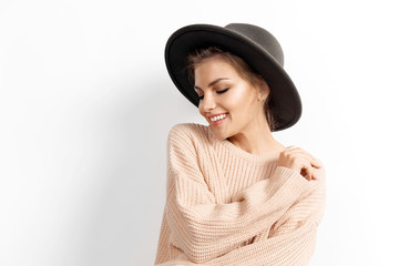 Portrait of smiling girl in knitted beige sweater and hat on white background. Warm photo shoot of pretty cheerful woman. Youth and autumn concept.