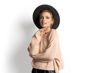 Wall Mural - Portrait of romantic girl in knitted warm sweater on white background. Pretty young female wearing modern autumn outfit. Warming up and youth concept.