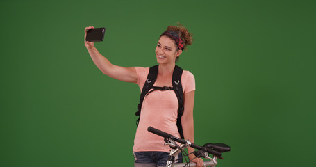 Millennial using smartphone to take selfie portrait on green screen