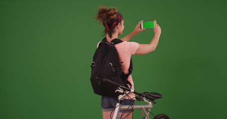 Woman in her 20s using smartphone to take photos on green screen