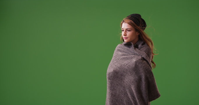Young woman wrapped up in blanket standing on green screen