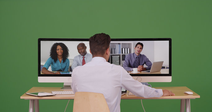 Associates having internet based web conference over video chat on green screen