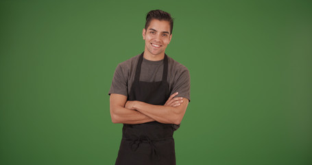 Happy handsome young Latino restaurant employee on green screen