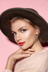 Beautiful model with fresh clean skin and red lips on pink background. Skincare and makeup concept.